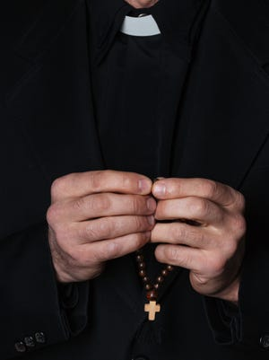 Hands of catholic priest holding rosary