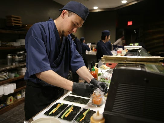 Jordan Stahf works on spicy shrimp tempura roll during