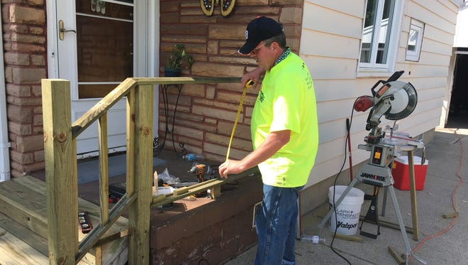 """A volunteer repairs a porch during the Port Huron Church of Christ's """"Mission Possible"""" project."""