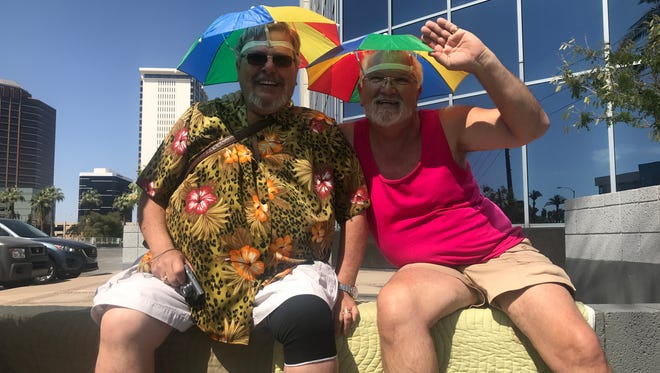 Brad Foulk and his partner Russ Chase sit on a ledge watching the Phoenix Pride Parade on Sunday, April 8, 2018.