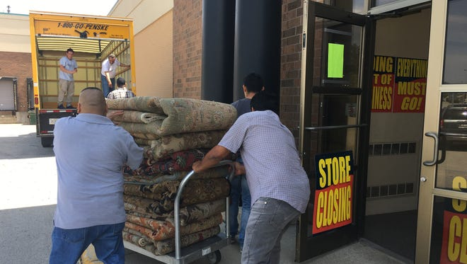 Employees of Shemiran Rugs cart rugs the Milwaukee-based importer sold to Bon-Ton Stores Inc. out of the Bay Park Square store after a pricing dispute arose with liquidators who bought Bon-Ton's assets.