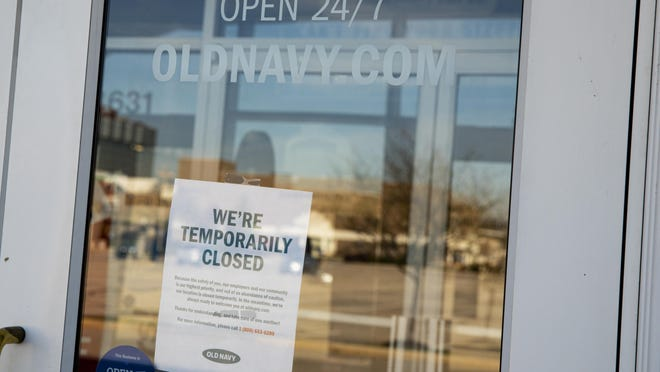 The empty parking lot is reflected in the door of temporarily closed Old Navy store in Indianapolis, Thursday, April 2, 2020. More than 6.6 million Americans applied for unemployment benefits the week of March 23, far exceeding a record high set just last week, a sign that layoffs are accelerating in the midst of the coronavirus. (AP Photo/Michael Conroy)