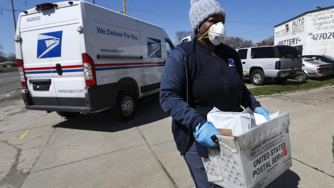 In this April 2, 2020 file photo a United States Postal worker makes a delivery with gloves and a mask in Warren. A group of states suing over service cuts at the U.S. Postal Service is asking a federal judge to immediately undo some of them, saying the integrity of the upcoming election is at stake.