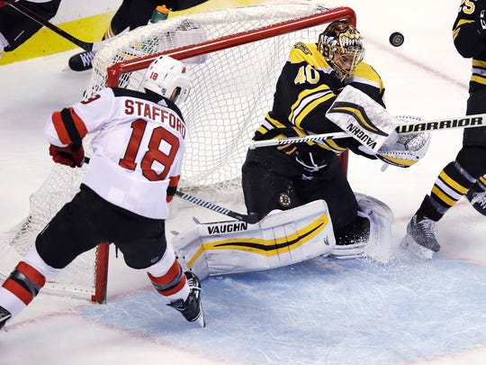Boston Bruins goaltender Tuukka Rask (40) makes a save on a shot by New Jersey Devils right wing Drew Stafford (18) during the first period of an NHL hockey game in Boston on Tuesday, Jan. 23, 2018.