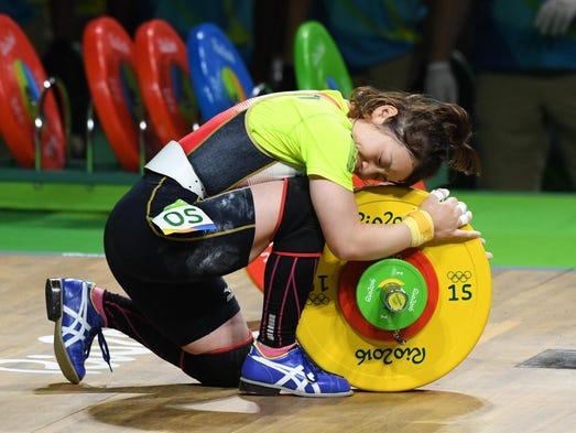 Hiromi Miyake (JPN) hugs the weights during the women's