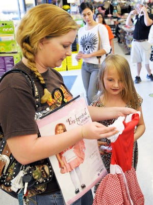 "Nicole Swanson, left, look for an alternative costume for her daughter, Brooke, 8, after finding out ""Elsa"" from Frozen costumes are all sold out as they get ready for Halloween at Party City, 1917 W. Caldwell Ave., Visalia."