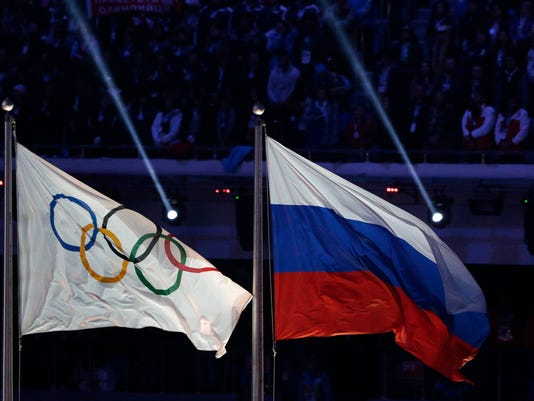 """FILE - In this Feb. 23, 2014 file photo, the Russian national flag, right, flies next to the Olympic flag during the closing ceremony of the 2014 Winter Olympics in Sochi, Russia. The word """"Russia"""" will appear on the Olympic uniforms worn by the athletes granted an exemption from the country's doping ban. More than 200 athletes are set to compete in Pyeongchang as an """"Olympic Athlete from Russia"""" if they can prove they aren't tainted by doping. (AP Photo/Matthias Schrader, File)"""