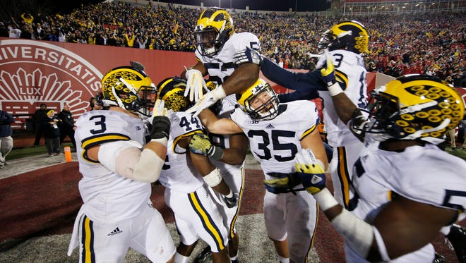 Michigan safety Delano Hill celebrates with teammates after making the last defensive play of the game to give Michigan the victory against the Indiana Hoosiers at Memorial Stadium. Michigan defeats Indiana in double overtime 48-41.