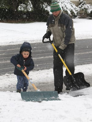 Baron Dulaney of Upper Nyack gets help from his son, Henry, 2, as they shovel their driveway Nov. 26, 2014.