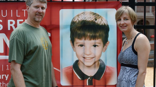 Chris and Hendrika Layton, parents of Ben Layton, stand next to a photo of him at the Ben's Red Swings complex in Salisbury.