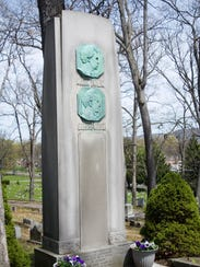 The file photo shows the grave marker with the plaques