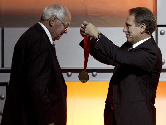 """Former Michigan State basketball coach Jud Heathcote, left, is presented with a medal by current Michigan State coach Tom Izzo as Heathcote is inducted into the National Collegiate Basketball Hall of Fame, Sunday, Nov. 22, 2009, in Kansas City, Mo.  Other inductees include Larry Bird, Earvin """"Magic"""" Johnson, Gene Bartow, Walter Byers, Travis Grant, Wayman Tisdale and Bill Wall."""