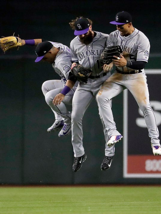 From left to right, Colorado Rockies' Gerardo Parra, Charlie Blackmon and Carlos Gonzalez celebrate after a baseball game against the Arizona Diamondbacks, Saturday, March 31, 2018, in Phoenix. (AP Photo/Matt York)