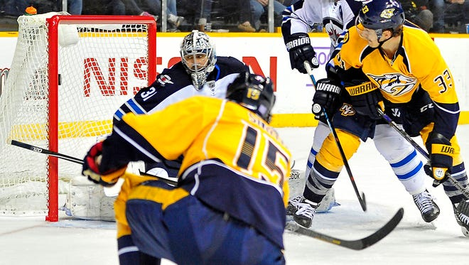Predators center Craig Smith (15) watches his shot fly past Jets goalie Ondrej Pavelec in the third period Saturday. It proved to be the game winner.