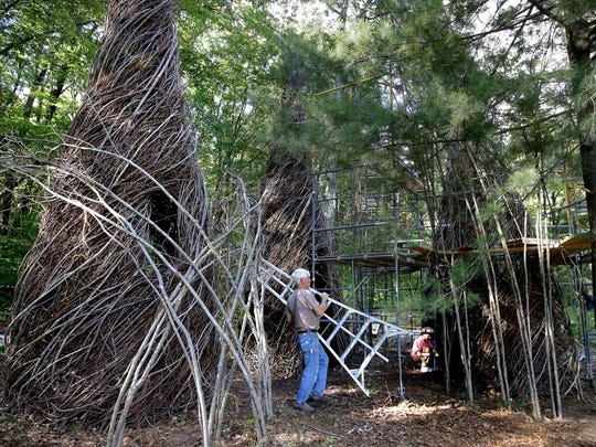 """In this Wednesday, Aug. 17, 2016 photo sculptor Patrick Dougherty carries a step ladder while constructing a sculptural installation """"The Wild Rumpus,"""" from branches and sticks on the grounds of the Tower Hill Botanic Garden, in Boylston, Mass. Dougherty's installation opens to the public Thursday, Aug. 25."""