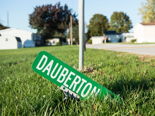A damaged street sign lies on the ground at New Oxford