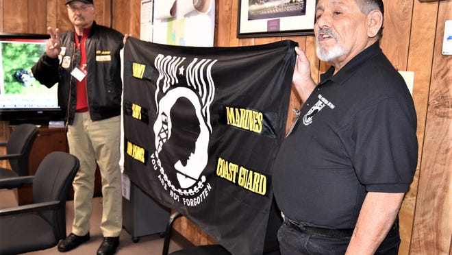Butch Chavez, right, founder of Pueblo POW/MIA Memorial, and retired Army Col. John Saenz, left, hold up the flag that ventured cross country through the 2019-2020 POW/MIA Flag 50-State Tour.