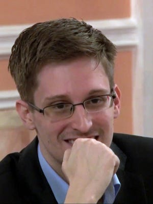 This file photo image made from video released by WikiLeaks on Friday, Oct. 11, 2013, shows former National Security Agency systems analyst Edward Snowden smiles during a presentation ceremony for the Sam Adams Award in Moscow, Russia.