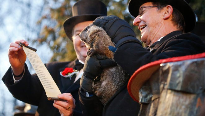 """Groundhog Club co-handler Ron Ploucha holds Punxsutawney Phil as Jeff Lundyholds holds the scroll during the annual celebration of Groundhog Day.  The handlers say the furry rodent has failed to see his shadow, meaning he's """"predicted"""" an early spring."""