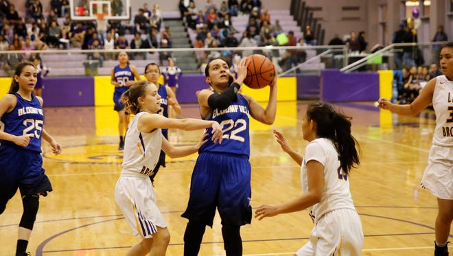 Bloomfield's Brandi Alcantar, No. 22 in blue, drives through the lane and knocks down a jumper against Kirtland Central during the first quarter of Thursday's District 1-5A game at Bronco Arena. The Bobcats, who clinched the District 1-5A title, have stepped up more on offense in their last four games.