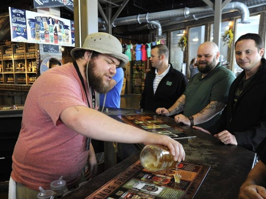 Anthony Nehr, left, pours moonshine samples for customers