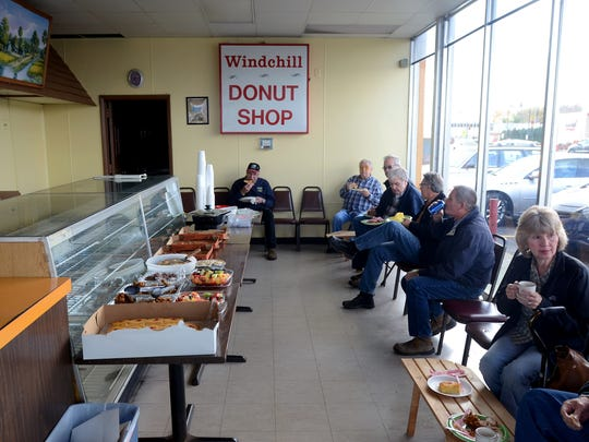 Regulars sit around and enjoy a spread of food on Windchill Donut Shop's last day Monday, Oct. 26, in Port Huron.