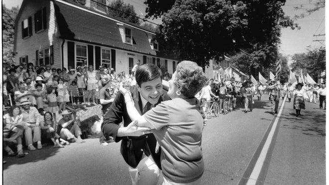 In 1980, Providence Mayor Vincent A. Cianci Jr. is embraced by a spectator along the line of march during the 1980 July Fourth parade in Bristol.