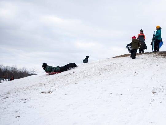 Kids line up on top of the sledding hill in the East