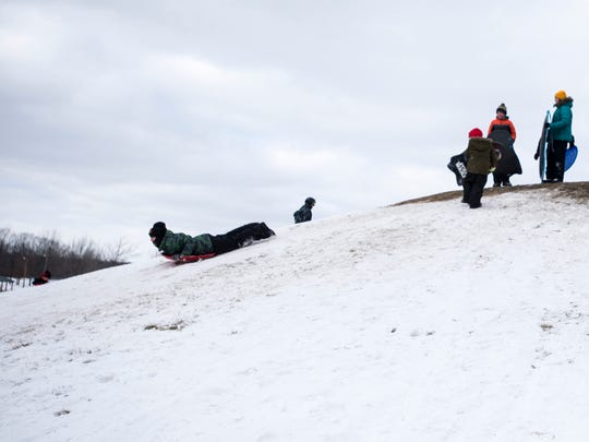 Kids line up on top of the sledding hill in the East China Township Park Tuesday morning. Monday's snowstorm dropped about 4.5 inches on the area, according to a representative from the National Weather Service.