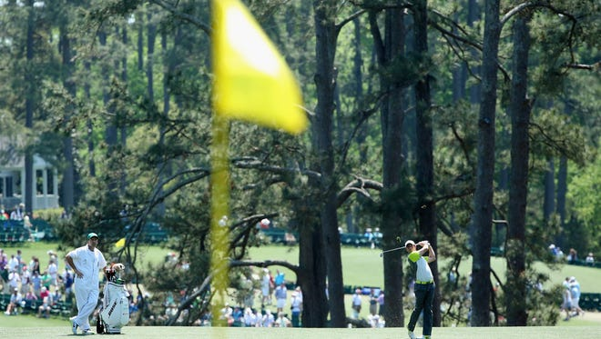 Rory McIlroy of Ireland hits a shot to the first green during the final round of the Masters at Augusta National Golf Club, an exclusive club that admitted its first female members in 2012.