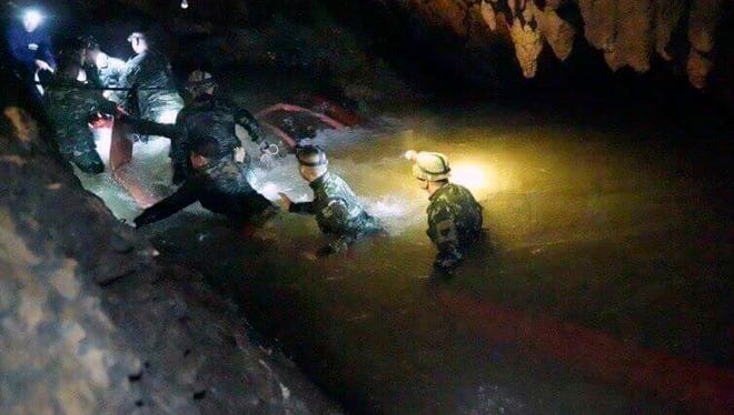 Thai rescue teams use headlamps to enter a pitch-black cave complex where 12 boys and their soccer coach went missing, in Mae Sai, Chiang Rai province, northern Thailand, Monday. The group was discovered late July 2 after 10 days totally cut off from the outside world, and while they are for the most physically healthy, experts say the ordeal has likely taken a mental toll that could worsen the longer the situation lasts.