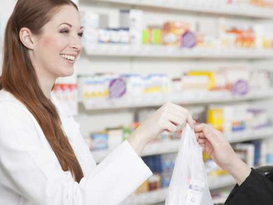 A pharmacy employees hands woman her prescriptions.
