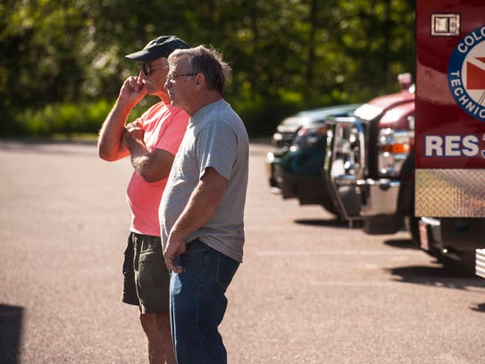 Rodney Dion's brothers, Gary, left, and Mike, watch