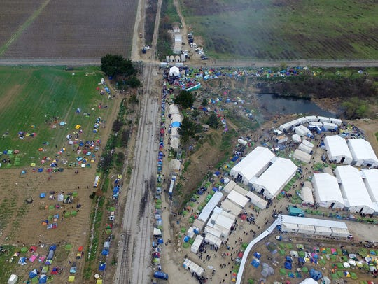 Tents of refugees and migrants stand next to a refugee