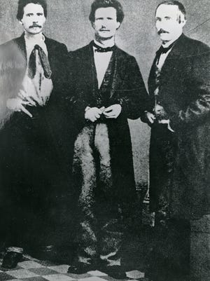 "Samuel Clemens, center, who began writing under the pen name Mark Twain as a reporter in Nevada, is flanked by A.J. Simmons and Billy Claggett in Virginia City. Nevada Historical Society A. J. Simmons, Samuel Clemmens (""Mark Twain"") and Billy Claggett in Virginia City. Photo courtesy Nevada Historical Society"