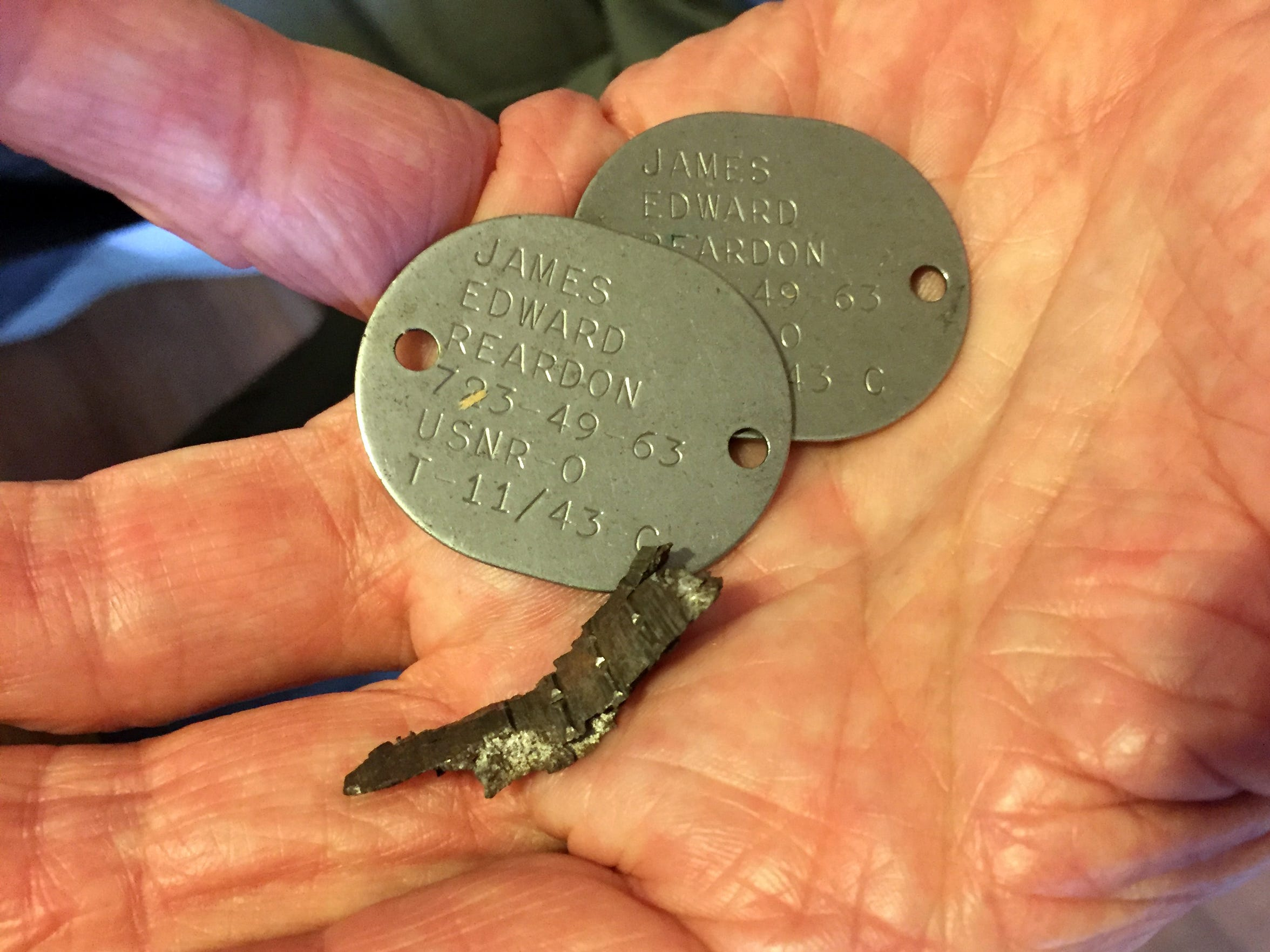 James Reardon holds his dog tags from WWII with a piece