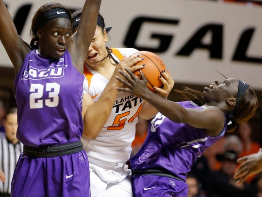 Oklahoma State's Kaylee Jensen (54) fights for the ball between Abilene Christian's Suzzy Dimba (23) and Lizzy Dimba (32) during the first round of the Women's NIT in Stillwater, Okla., Thursday, March 16, 2017.