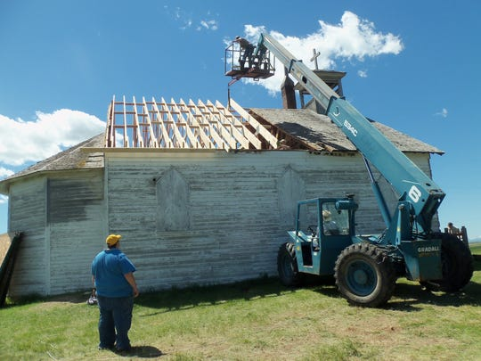 Volunteers worked to replace the roof of Sacred Heart Church in July, 2013.