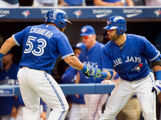 Toronto Blue Jays Melky Cabrera is congratulated by teammate Jose Bautista after he hit a solo home run against the Texas Rangers in the seventh inning of a baseball game in Toronto, Sunday, July 20, 2014. (AP Photo/The Canadian Press, Fred Thornhill)