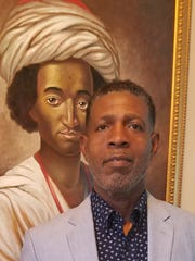 Willis Hakim Jones is photographed here in front of a painting of an 18th century African American Muslim. His collection of documents and artifacts from the Gullah GeeChee culture of South Carolina is opening Saturday at the Riley House Museum and at the Anderson-Brickler Gallery.