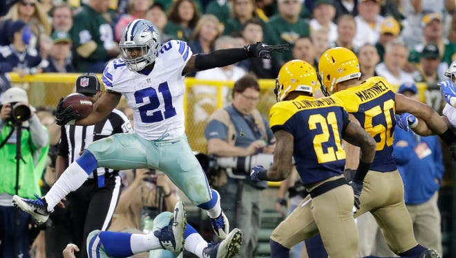 Dallas Cowboys running back Ezekiel Elliott lunges for a first down against the Green Bay Packers at Lambeau Field.