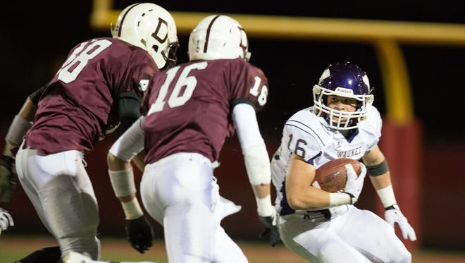Waukee High School's Pat Gray (16) looks to get away from Dowling's Eric Austin (48) and Nick Wilson (16).