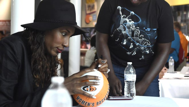Lisa Leslie, former WNBA basketball player and 2015 Women's Basketball Hall of Fame inductee, left, signs a ball for a fan during an autograph session Saturday.