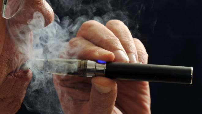 Torin Halsey, AP FILE - In this Jan. 17, 2014 file photo, a smoker demonstrates an e-cigarette in Wichita Falls, Texas. Soon, the Food and Drug Administration will propose rules for e-cigarettes. The rules will have big implications for a fast-growing industry and its legions of customers. (AP Photo/Wichita Falls Times Record News, Torin Halsey, File)