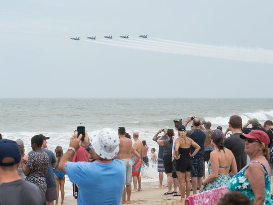 Crowds of beachgoers watch the Blue Angels perform