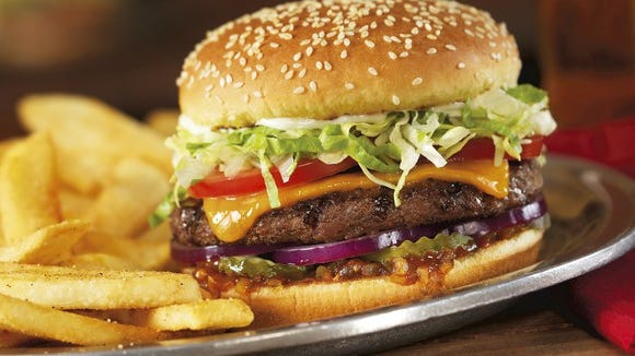 A gourmet cheeseburger and french fries on a metal plate from Red Robin.
