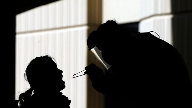 Brian Gill administers a coronavirus test Oct. 16, 2020, at the University of Texas at El Paso campus. With a spike in cases in El Paso, more people are flocking to testing centers.