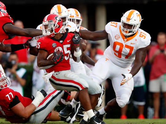 Georgia running back Brian Herrien (35) spins away from the grasp of Tennessee defensive lineman Paul Bain (97) during the second half of an NCAA college football game Saturday, Sept. 29, 2018, in Athens, Ga. Georgia won 38-12. (AP Photo/John Bazemore)