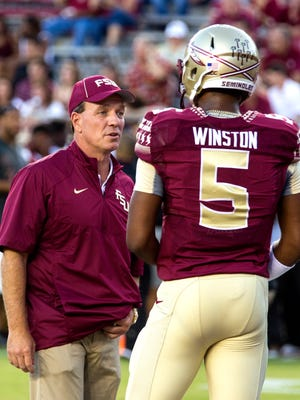 Florida State coach Jimbo Fisher talks to suspended Heisman quarterback Jameis Winston, who dressed in full pads for pre game warm ups, sending him back to the locker room to change on Saturday vs. Clemson.