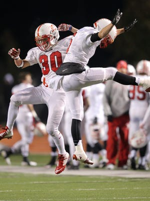 Center Grove players Titus McCoy, left, and Devon Hensley celebrate their team scoring a touchdown to go up 21-14 over Ben Davis during the IHSAA Semi-State game held at Ben Davis High School on Friday, Nov. 14, 2014.